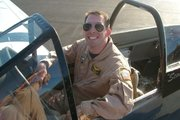 Nathan Mackey sitting in a North American P-51D Mustang