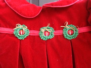 Crocheted wreaths on baby's dress