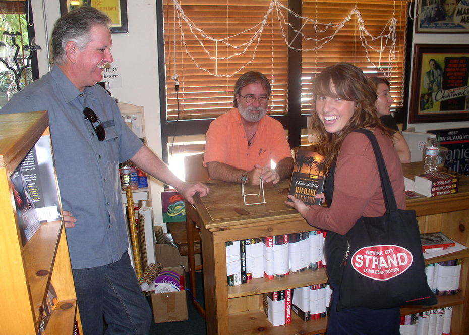 Mystery fan Bob Palty looks on as Alexis Bolter buys the last copy of Micheal Haskins' book, Chain' the Wind, at Mystery Bookstore in Westwood, Calif