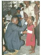 Bishop Albert praying for children
