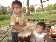 Little child playing tabla Instrument