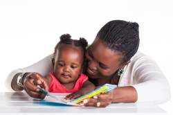 child reading book with mom