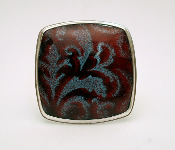 red and blue scrollwork brooch