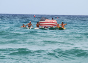 Surfers holding up the flag