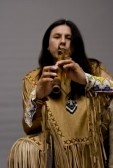 3827986-portrait-of-a-native-american-playing-at-a-flute-in-a-studio