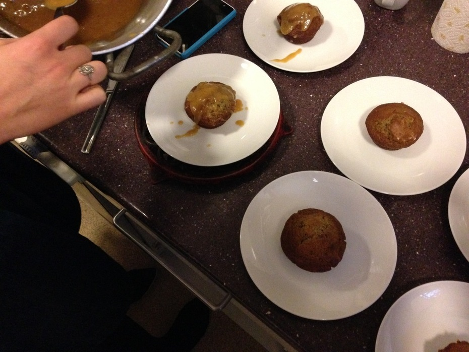 Adding pear caramel sauce to sticky toffee puddings