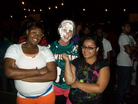 Young Life kids celebrate smashing a pie in their leader's face