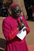 Odama kneels in the hot, Gulu sun