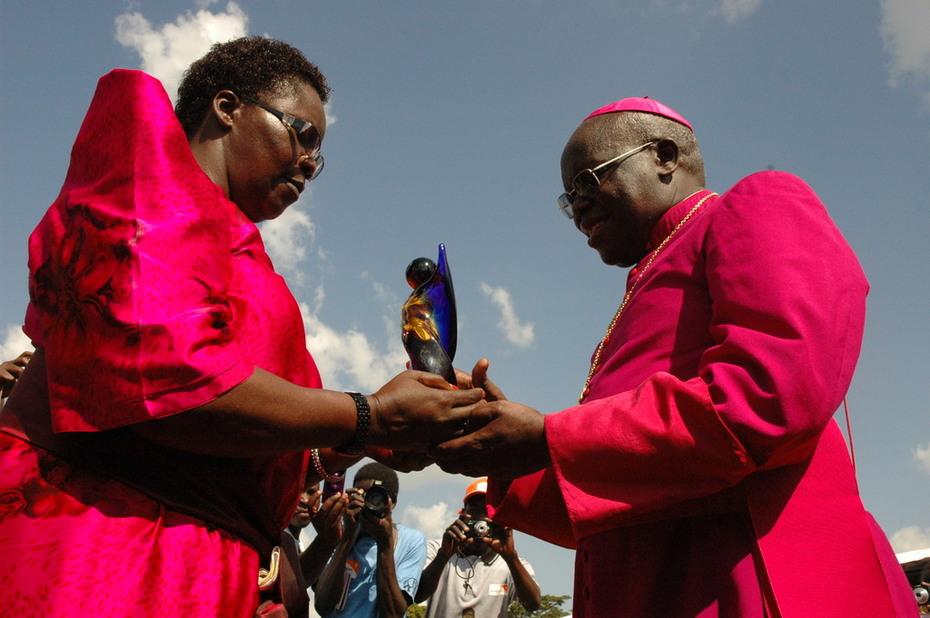 Hon. Rebecca Amuge Otengo hands trophy to Archbishop Odama