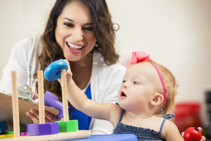 Picture of mother and infant playing with a toy and smiling
