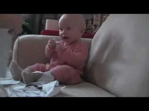 Bebê dando gargalhadas ao rasgar o papel