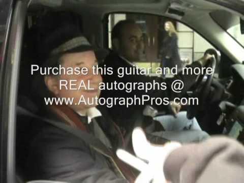 Paul Simon of Simon & Garfunkel stops to sign a guitar.