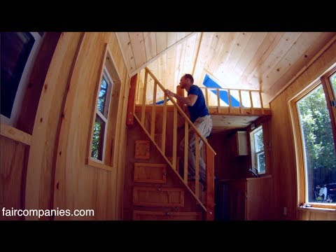 Tiny home packs storage stairs, 2 lofts, tub in 136 sq ft